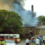 Colour photograph of smoke coming out of the brewery roof with crowds and fire brigade outside.