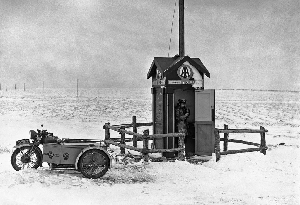 Black and white image showing AA man with his motor bike and side-car near using a AA phone box on Bodmin Moor in the snow