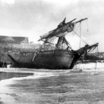 Black and white photograph showing ship run aground on beach.