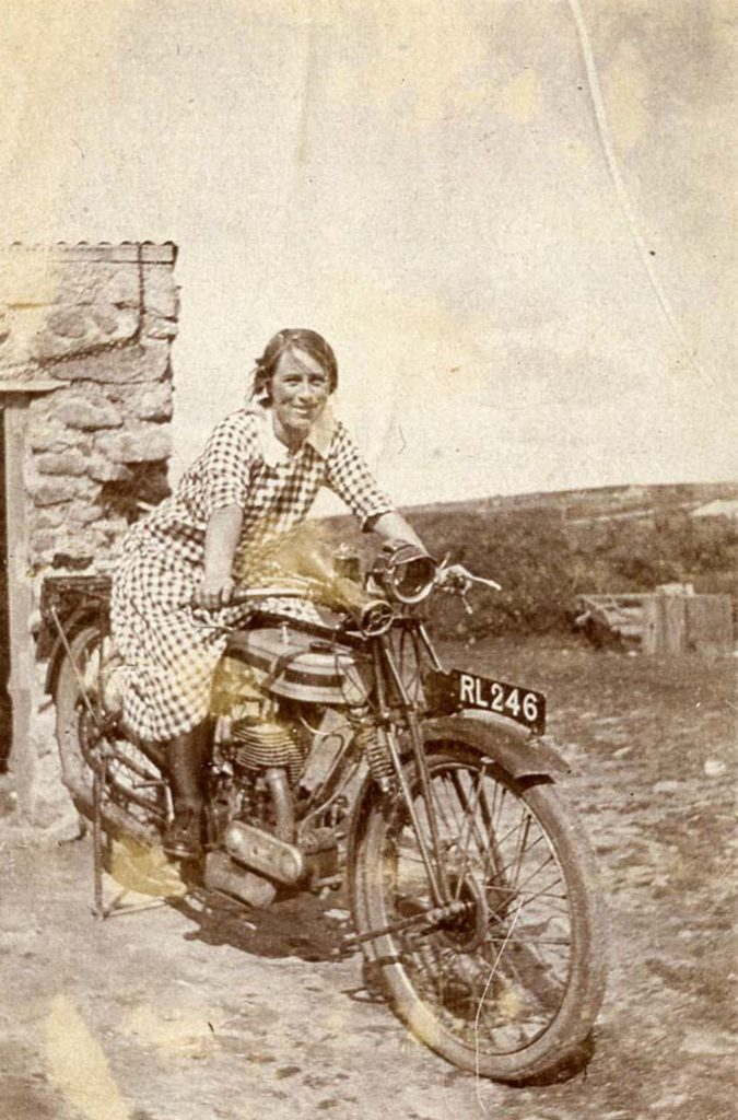 Photograph of girl on an motorbike in the early 20th century with registration number RL246.