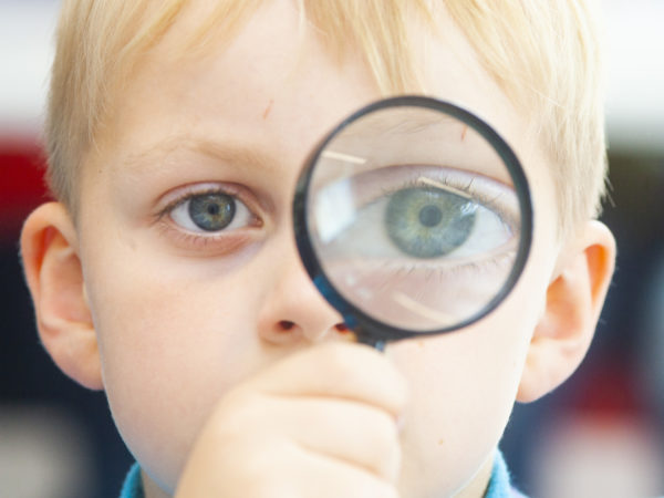 Photograph of child with magnifying glass.