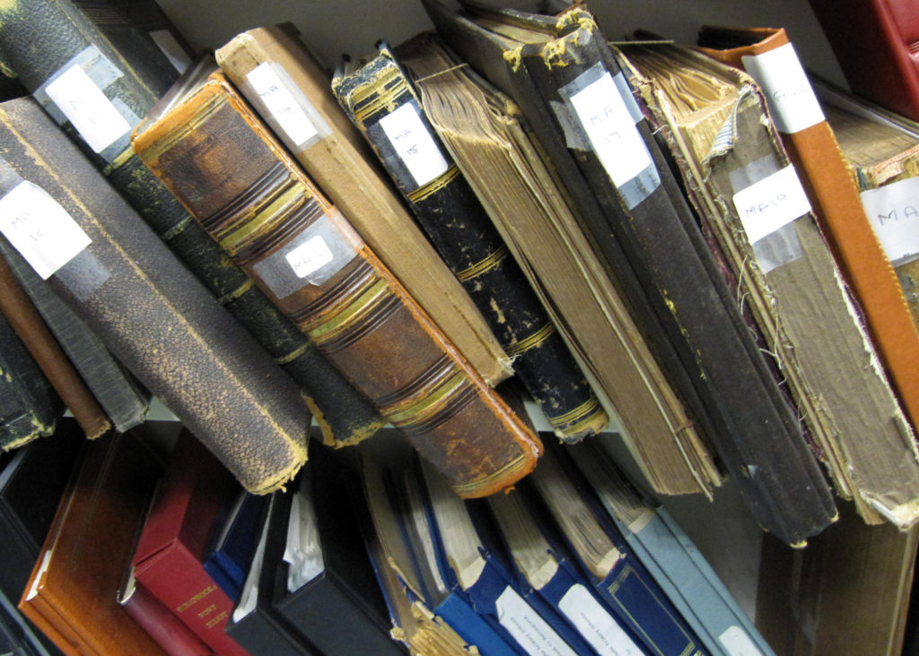 A photograph showing various files and volumes in a solicitor's office prior to being donated to Kresen Kernow.