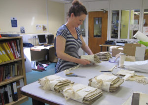 Photograph of a member of staff packaging documents.