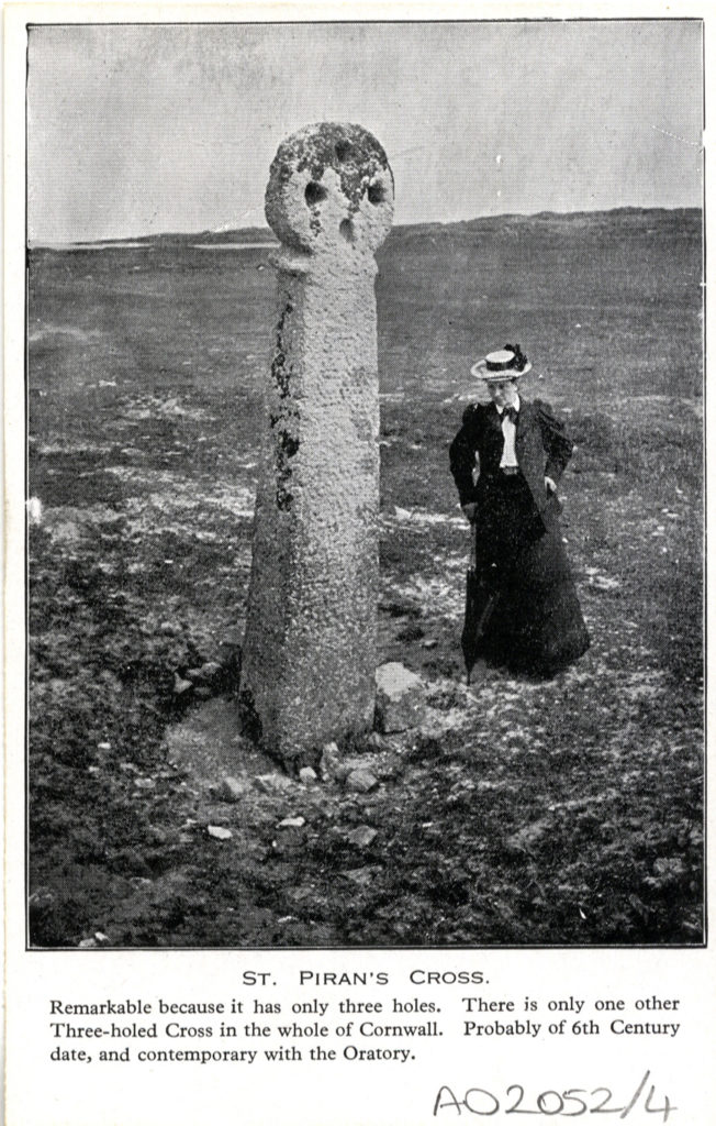 Postcard of a lady standing next to St Piran's Cross, dated 1929.