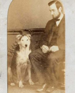 Sepia photographic portrait of man with dog.