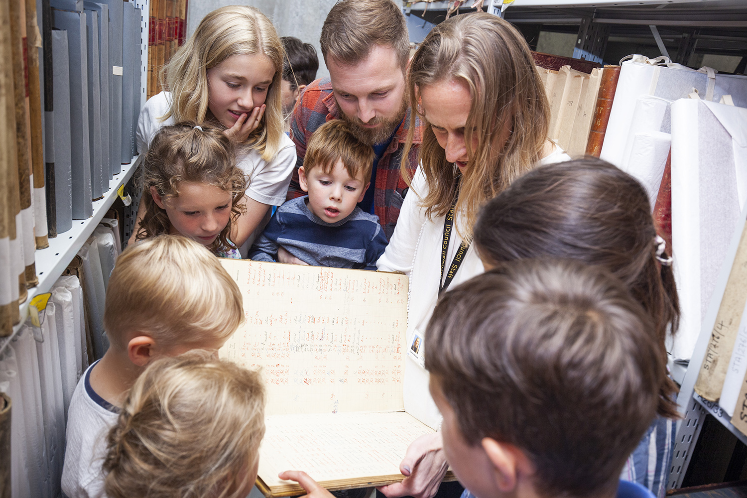 Photo of group of adults and children looking at a large book.