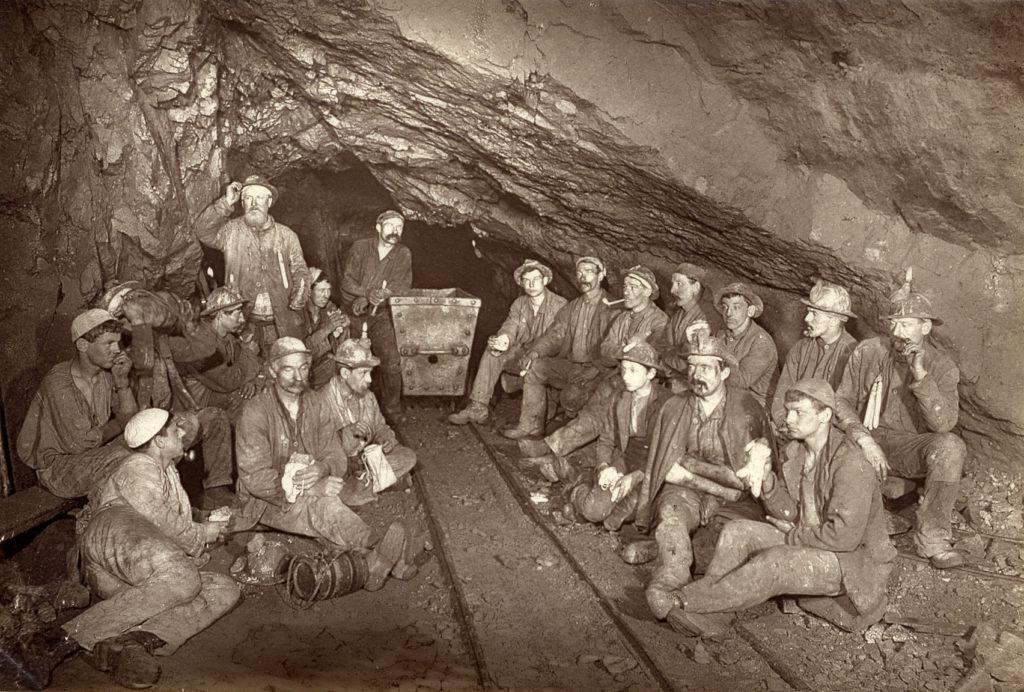 Sepia photograph of Cornish miners underground eating pasties.
