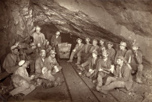Sepia photograph of Cornish miners underground eating pasties.
