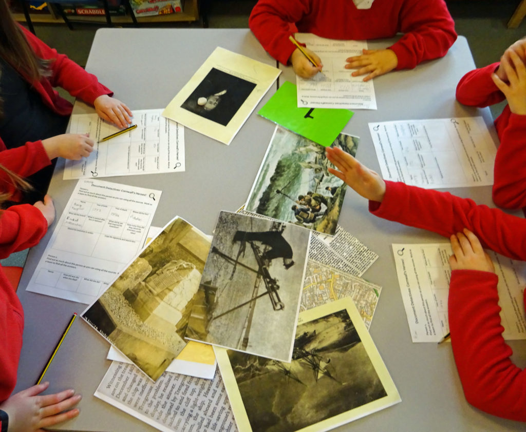Photograph of children in a classroom looking at a range of documents, including photos and maps.