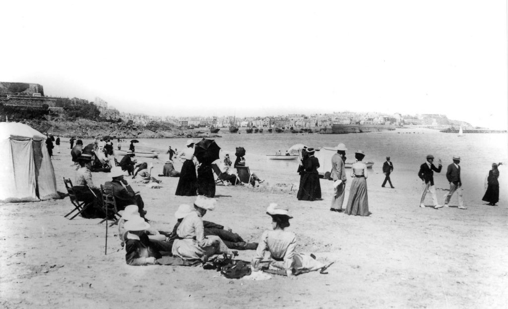Black and white photograph showing people on the beach in Victorian or Edwardian clothing.