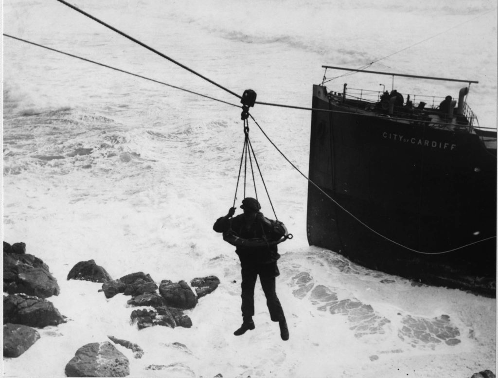 Photograph showing man hanging over sea being rescued from shipwreck using a breeches buoy.
