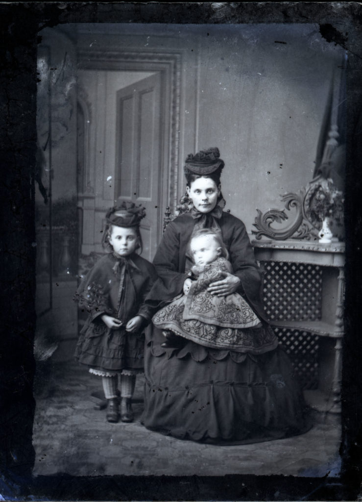 Victorian photographic portrait of lady with a child and a baby in elaborate clothing.