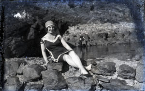 Black and white photograph of lady in bathing suit sitting on rocks.