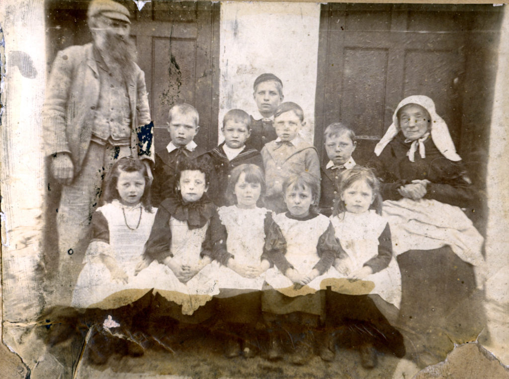 Poor condition photograph of a Dame School with children in Victorian clothing.