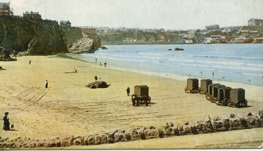 Coloured postcard showing beach with bathing machines.