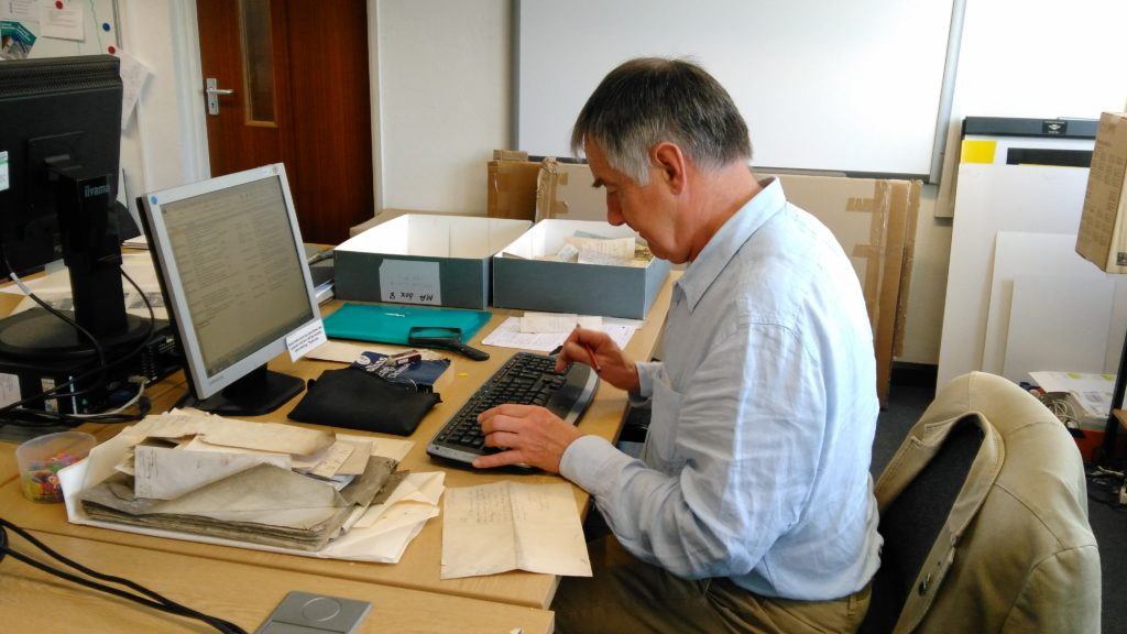 Photograph of male volunteer typing at a computer.