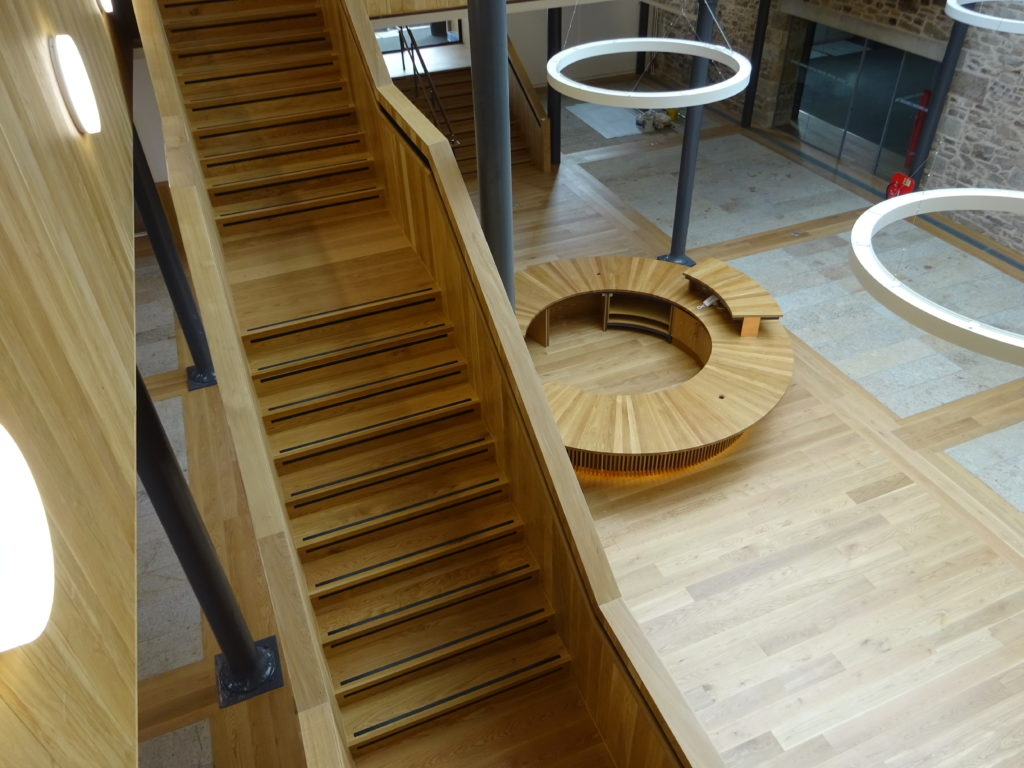 Photograph of the inside of Kresen Kernow showing oak staircase, flooring and reception desk and granite flooring.