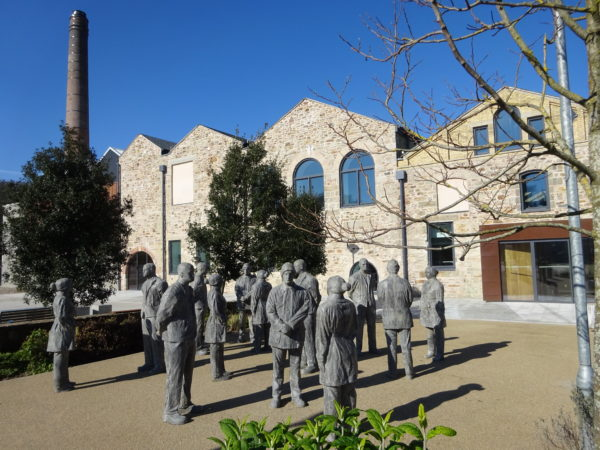 Photograph showing outside of Kresen Kernow building with statues and trees and chimney visible.