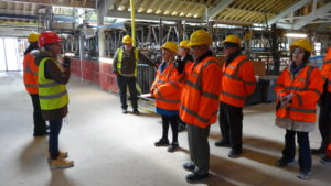 Photograph of group of people on tour of Kresen Kernow building wearing high visibility clothing and helmets.