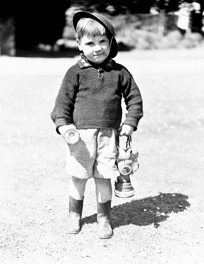 Black and white photograph of small boy holding gas mask wearing tin helmet.