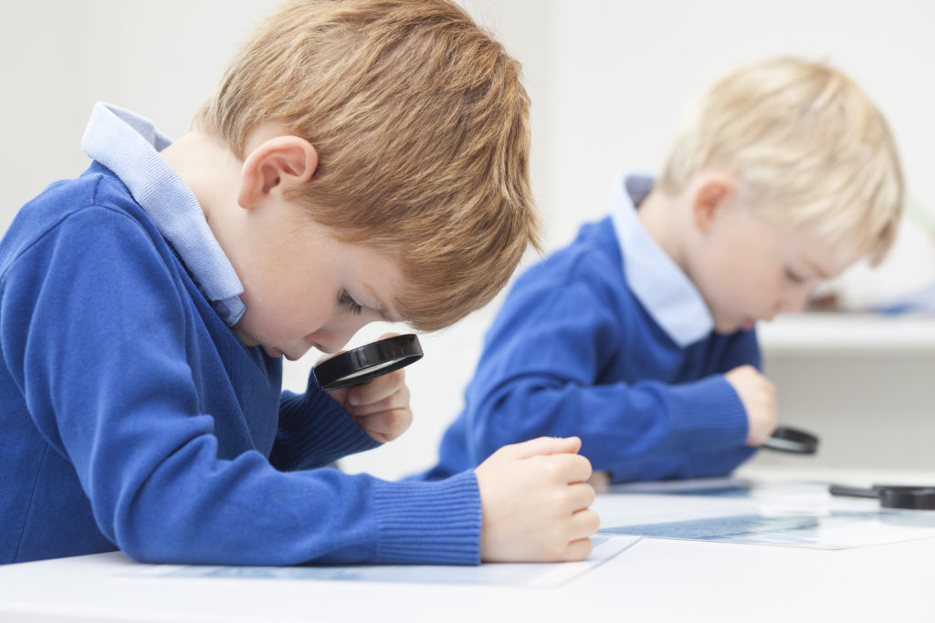 Photograph of two young boys in school uniform looking through magnifying glasses.