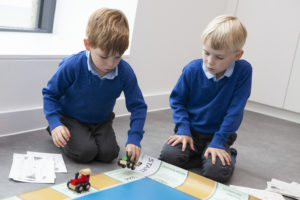 Photograph of two young boys playing with board game.