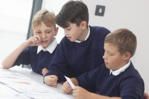 Photograph of school boys looking at documents.