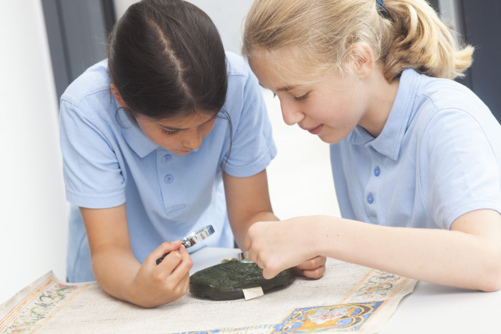 Photograph of two girls looking at a wax seal through magnifying glasses.