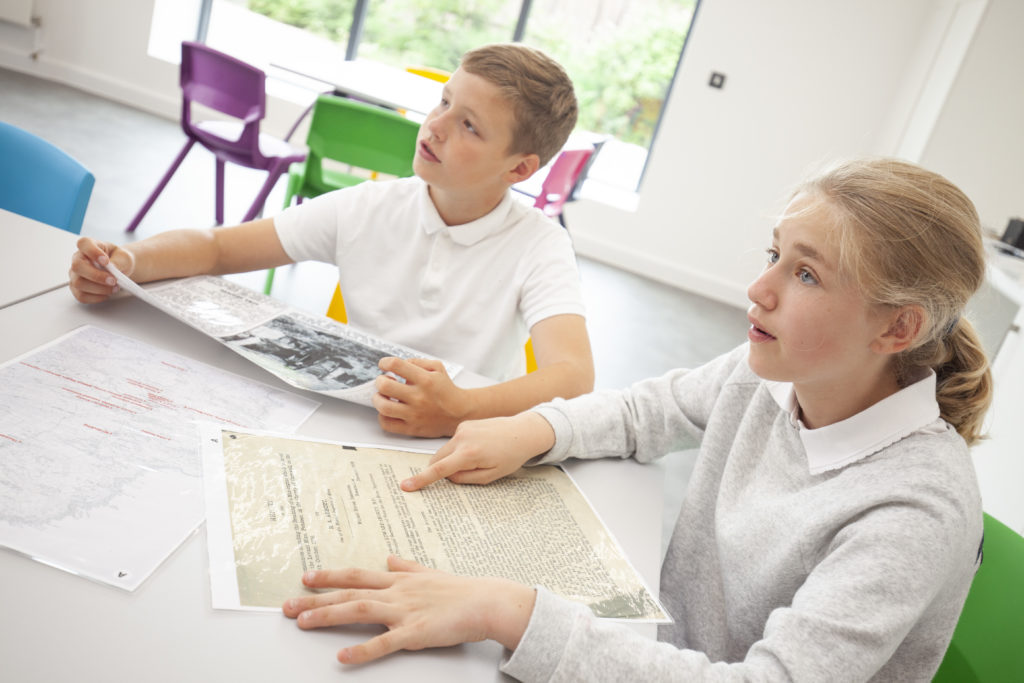 Photograph of two children looking at copies of documents.