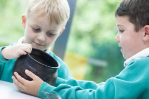 Photograph of two boys holding a replica pot.