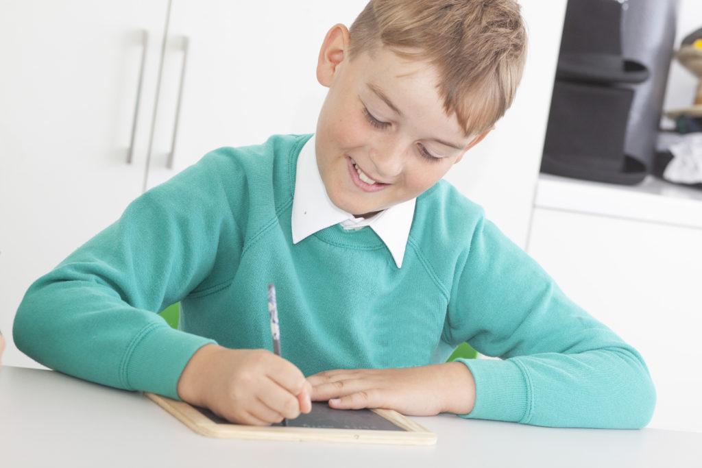 Photograph of boy writing on slate.