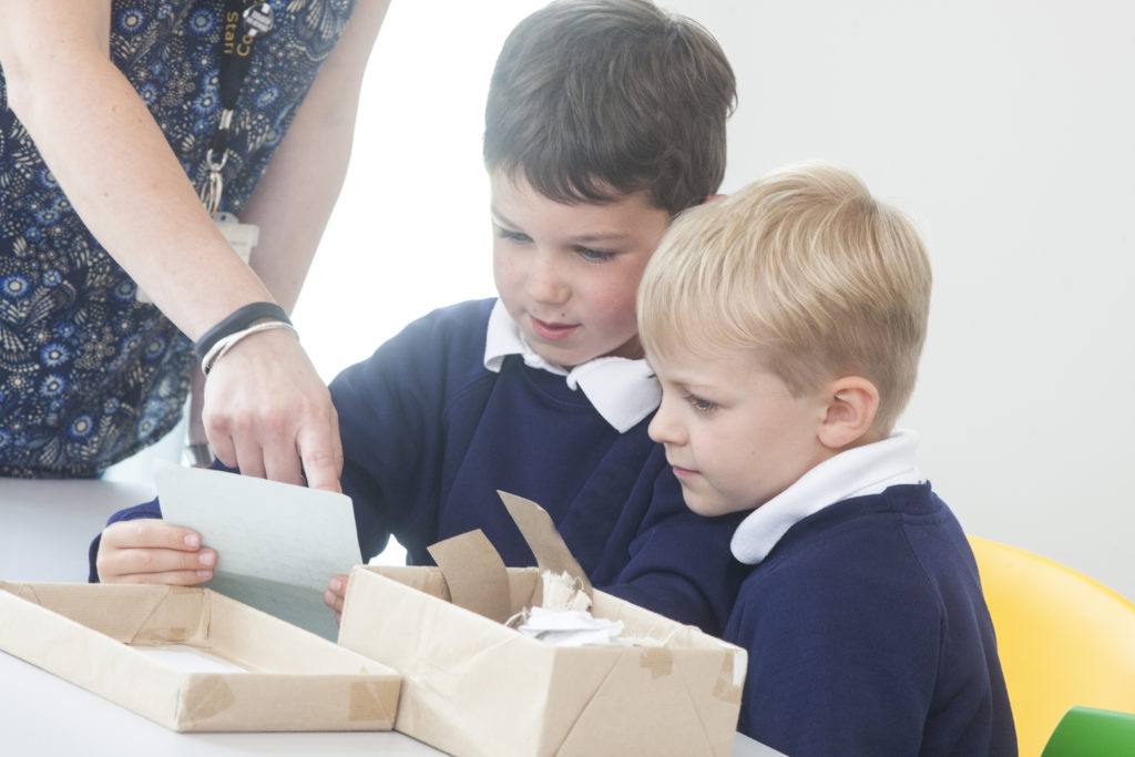 Photograph of two boys exploring a box of items.