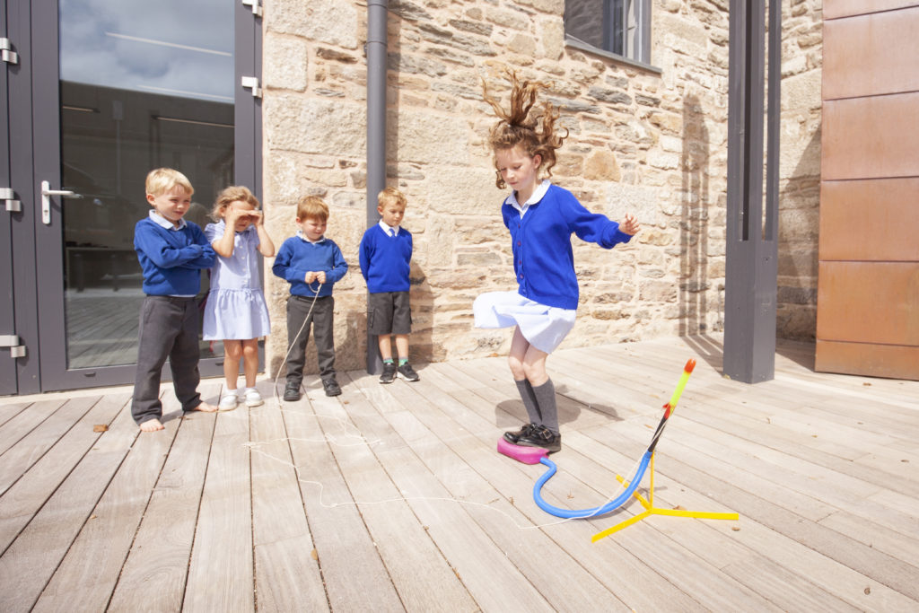Photograph of group of children outside playing with a stomp rocket.