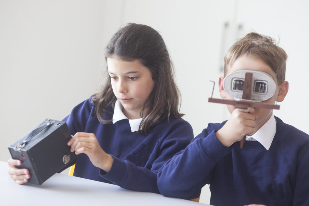 Photograph of children examining old cameras and a stereoscope.