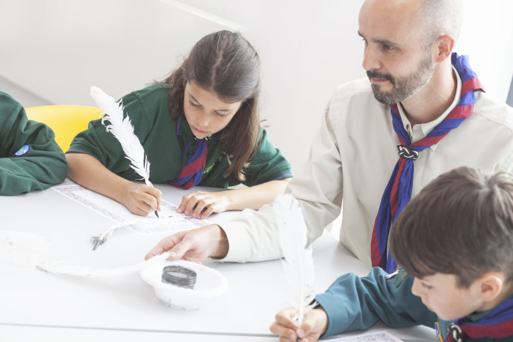Photograph of Cub leader and Cubs writing with quill pens.