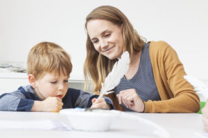 Photograph of mother and son with quill pen.
