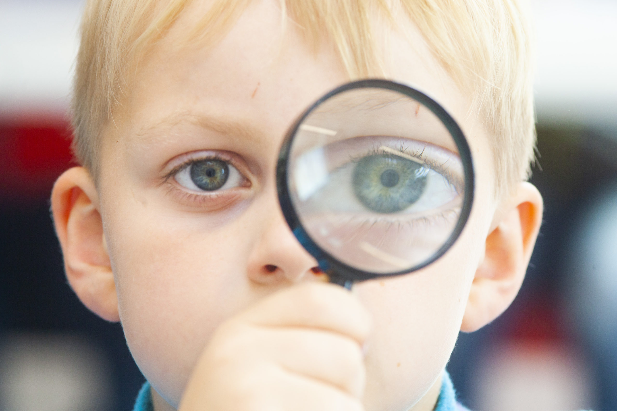 Photograph of young child looking through magnifying glass.