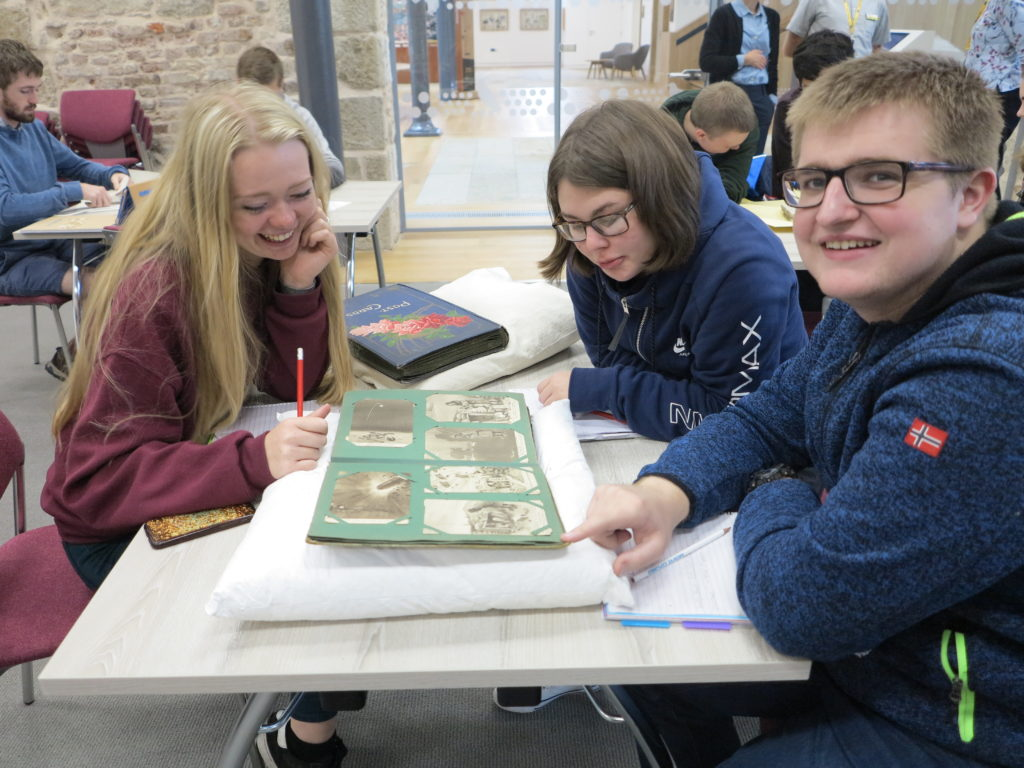 Photograph of group of students looking at document.