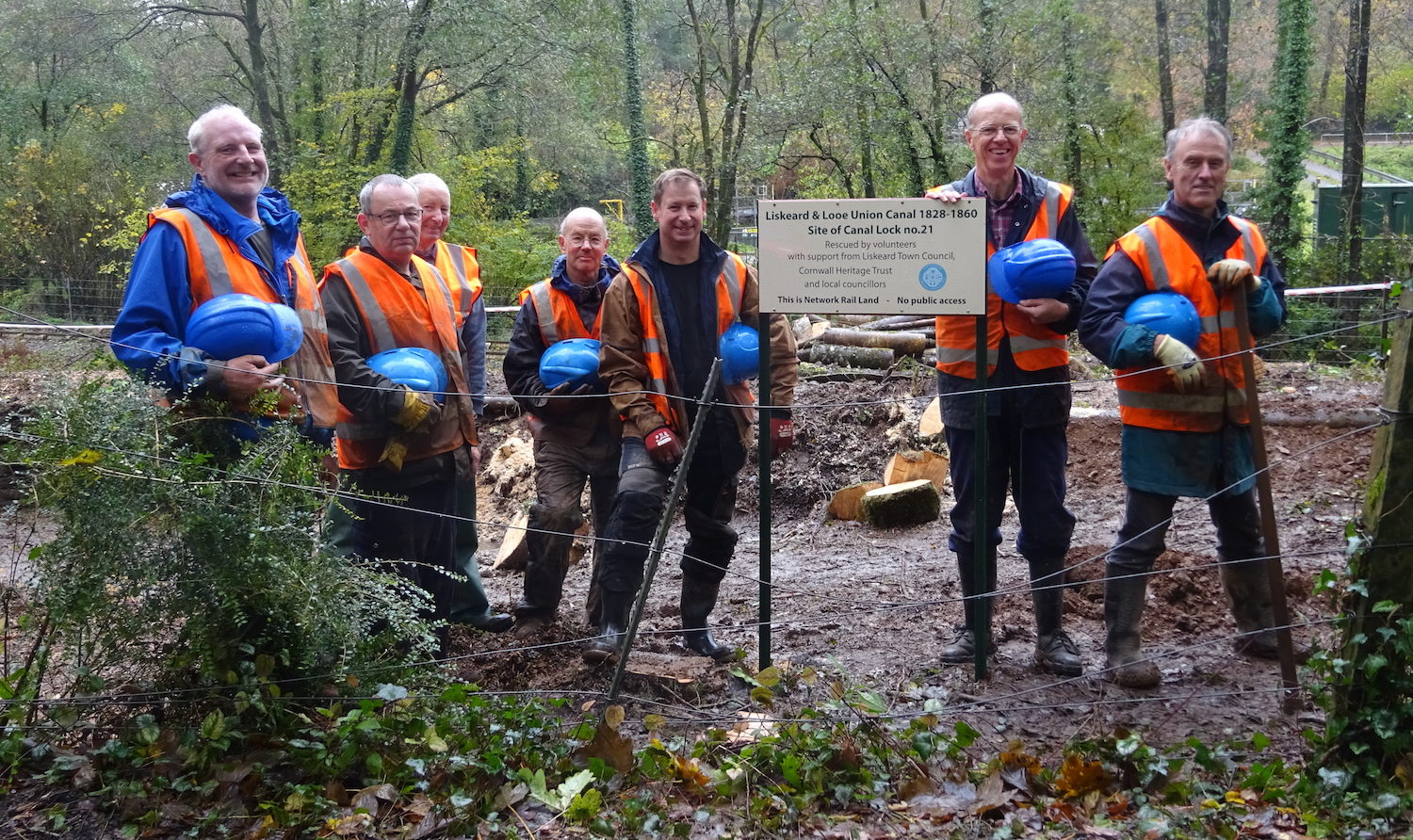 Photograph of group of men in high visibility vests outdoors near muddy canal.
