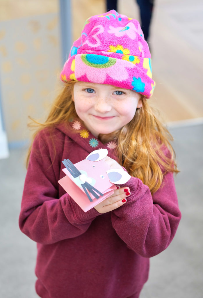 Photograph of child wearing hat showing off finger puppet