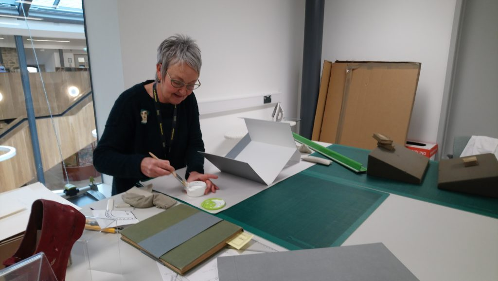 Photograph of female volunteer gluing a book mount together