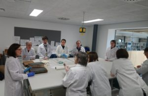 Photograph of group of volunteers in white coats taking part in archive preservation training