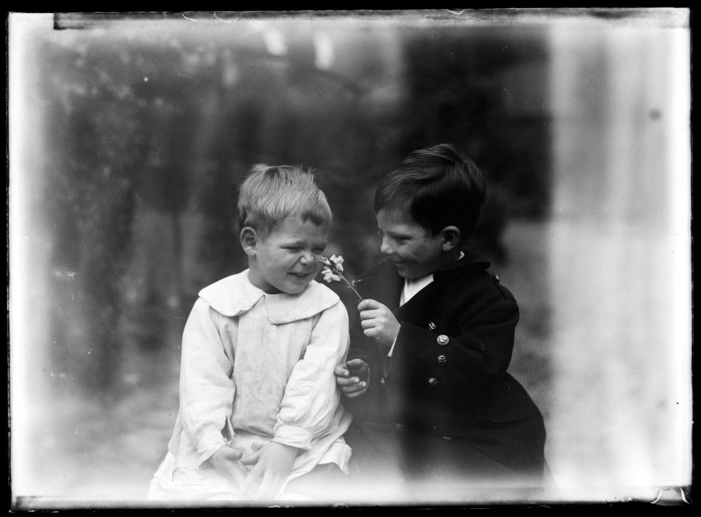 Black and white historic photo of two young boys smelling a flower.