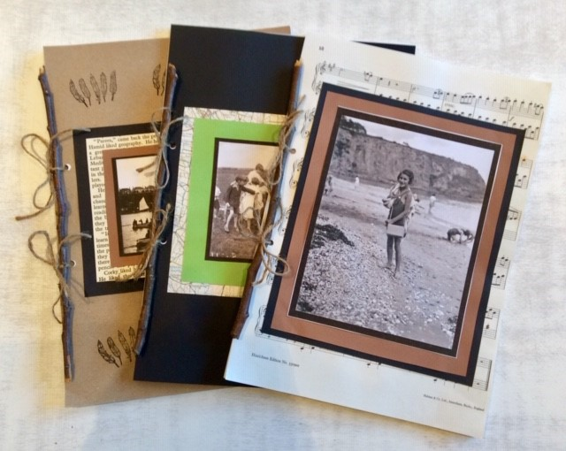 Colour photo of three handmade books with historic photos on their covers.