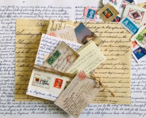 Colour photograph of montage of letters, postcards, stamps and a handmade book.