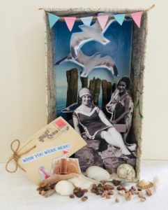 Photograph of a handmade beach scene in a cardboard box showing a lady sitting on the rocks, some seagulls and shells.