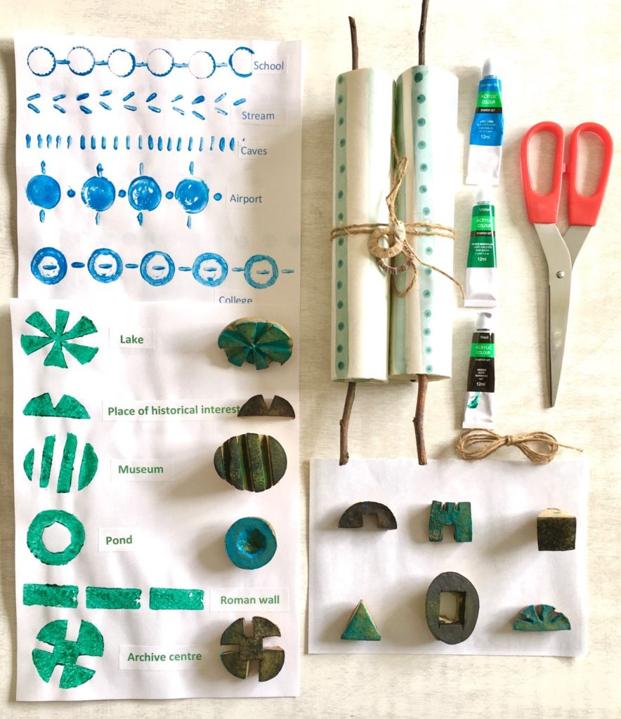 Colour photo showing potato printing, scissors, paint and paper.