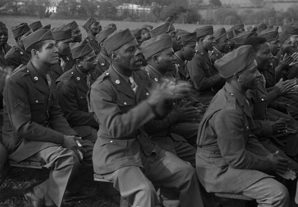 Black and white photograph of Black soldiers clapping.
