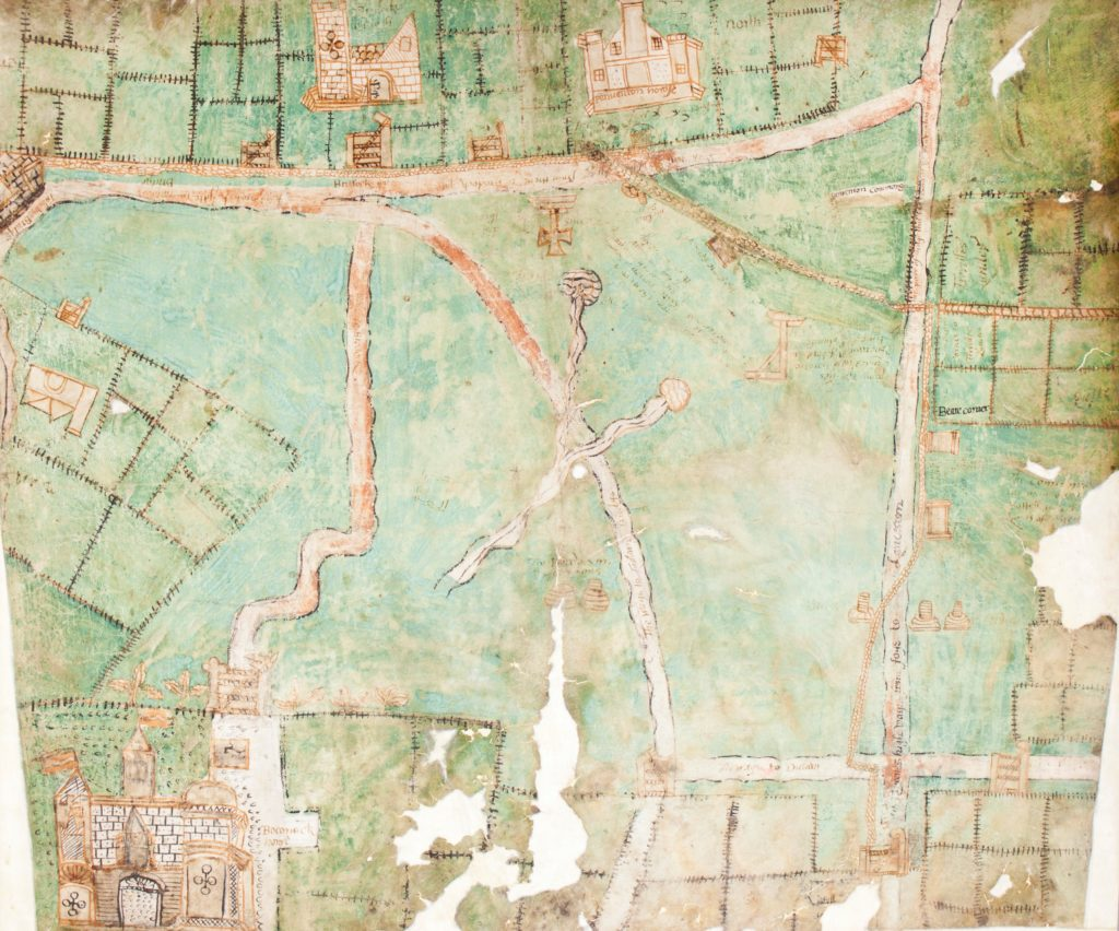 Photograph of early hand drawn map showing green fields and brown buildings.