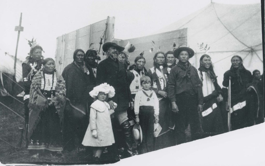 Black and white photograph showing Native Americans and children with Buffalo Bill